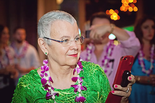 Picture of La Rita Mason: a woman facing to the right, with short gray hair wearing a green patterned shirt and a lei of purple flowers. She is holding a red phone.